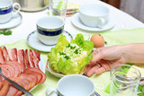 Śniadanie Wielkanocne na stole, kobieta układa jedzenie, jajka.