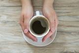 Filiżanka czarna aromat kawa w kobiety ręce na drewnianym tle