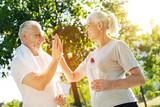 Pozytyw starzejąca się para odpoczywa w parku po jogging