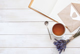 Top view of a cup of tea, lavender, notebook and love letter on a white wooden background. Herbal Tea Letter Note Lavender Love