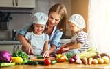 Zdrowe odżywianie. Szczęśliwa rodziny matka i dzieci przygotowywali jarzynowej sałatki