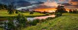 Panoramiczny zachód słońca nad rzeką Aln / The River Aln biegnie przez Northumberland z Alnham do Alnmouth. Widziany tutaj w panoramie poniżej miasta Alnwick i zamku na tle nieba, jak zachody słońca