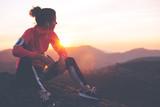 Sportowa kobieta odpoczywa po ciężkiego szkolenia w górach przy zmierzchem. Sportowe ciasne ubrania.