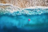 Widok z lotu ptaka szczupły kobiety dopłynięcie na różowym pływanie pierścionku w przejrzystym turkusowym morzu w Oludeniz, Turcja. Lato seascape z dziewczyną, piękne fala, kolorowa woda przy zmierzchem. Widok z góry z drona