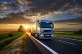 Ciężarowy jeżdżenie na asfaltowej drodze w wiejskim krajobrazie przy zmierzchem z ciemnymi chmurami
