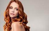Piękna wzorcowa dziewczyna z długim czerwonym kędzierzawym włosy. Czerwona głowa. Pielęgnacja i uroda produktów do pielęgnacji włosów