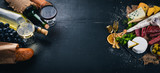 Butelka wina, serów i tradycyjnych kiełbasek na drewnianym tle. Ser brie, ser pleśniowy, gorgonzola, fuete, salami. Wolne miejsce na tekst. Widok z góry.