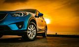 Niebieski samochód kompaktowy SUV ze sportem i nowoczesnym designem zaparkowanym na betonowej drodze nad morzem o zachodzie słońca. Technologia przyjazna dla środowiska. Koncepcja sukcesu w biznesie.