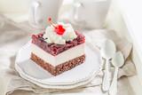 Wyśmienicie galaretowy wiśnia tort na bielu talerzu z śmietanką