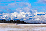 Scenic fresh snow on moutains and farm field with irrigation wheel move in Flathead Valley, Montana