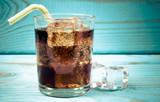 Słodki, gazowany napój z lodem na niebieskim tle.
