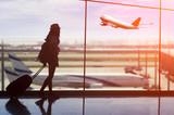 Młoda kobieta stoi blisko okno na lotnisku i ogląda samolot przed odjazdem.