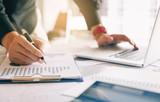 Biznesmena mienia pióro i wskazywać papierowej mapy podsumowanie analizuje rocznego raport biznesowy z używać laptop przy pokoju biurowym biurkiem.