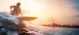 Surfer jeździ fal oceanu podczas zachodu słońca. Sport ekstremalny i koncepcja aktywnego stylu życia