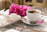 Zakończenie ranek kawa, marshmallows i piękni różowi peonia kwiaty na światło stole ,. Przytulne śniadanie w dniu matki lub kobiety.