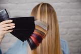 Mistrz pokazuje paletę kolorów włosów na tle włosów klienta.