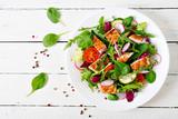 Sałatka ze świeżych warzyw z grillowaną piersią kurczaka - pomidory, ogórki, rzodkiewka i mix liści sałaty. Sałatka z kurczakiem. Zdrowe jedzenie. Widok z góry