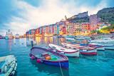 Mistyczny krajobraz portu z kolorowych domów i łodzi w Porto Venero, Włochy, Liguria w godzinach wieczornych w świetle latarni