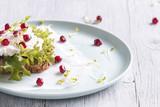 Kanapka z białym serem, sałatą i owoc granatu, na talerzu, który stoi na biały drewniany stół.
