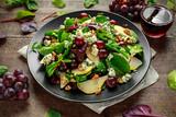 Świeże gruszki, sałatka z sera pleśniowego z mieszaniną warzyw zielonych, orzechy włoskie, czerwone winogrona. zdrowe jedzenie