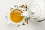 nalewanie herbaty z czajniczek do kubka na biały stół
