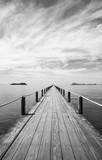 Czarny i biały krajobraz drewniany most w błękitnym morzu na tropikalnej plaży.