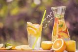 Zimny napój z owocami, kawałkami owoców i cytrusów, sprayem lecącym ze szklanki z napojem na naturalnym tle ogrodu. letni nastrój wakacyjny.
