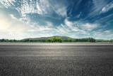 Asfaltowa droga i góra z niebo chmur krajobrazem przy zmierzchem