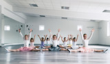 Taniec choreograficzny przez grupę pięknych młodych baletnic praktykujących podczas lekcji w klasycznej szkole baletowej.