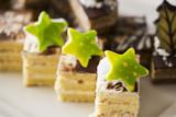 Ciasto biszkoptowe, ozdobione śmietaną i białą czekoladą na białym talerzu. Selektywna ostrość