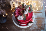 Uroczy czerwony tort z różami na świątecznym tle.