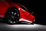 Nowożytny czerwony sporta samochód w świetle reflektorów na czarnym tle.