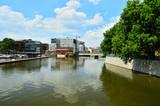 Rzeka płynąca przez miasto, mosty i drzewa nad brzegiem.