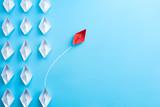 Grupa białego papieru statek w jeden kierunku i jeden czerwień papieru statku wskazuje w różnym sposobie na błękitnym tle. Biznes dla innowacyjnej koncepcji rozwiązania.