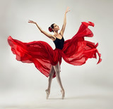 Balerina. Młoda, zgrabna kobieta baletnica, ubrana w profesjonalny strój, buty i czerwona spódnica w stanie nieważkości demonstruje umiejętność tańca. Piękno klasycznego tańca baletowego.