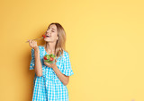 Happy slim woman with salad on color background. Weight loss diet