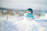 Mały bałwan w czapce i szalik na śniegu w zimie. Kartka bożonarodzeniowa z uroczym bałwanem, kopii przestrzeń