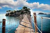 Drewniany most z widokiem na morze prowadzi do wyspy z palmami. To most linowy. Znajduje się na wyspie Zakynthos w Grecji.