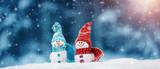 małe snowmans z dzianiny na miękkim śniegu na niebieskim tle