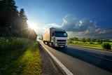 Biel ciężarówka przyjeżdża na asfaltowej drodze w wiejskim krajobrazie w promieniach zmierzch