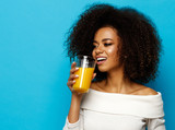 Beautiful african american girl with copy space drinking a orange juice