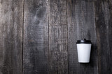 Take away coffee in paper cup on wooden background