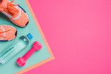 Flat lay with sport equipment on pink background