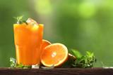 Świeży sok pomarańczowy w szkle z plasterkami pomarańcze na drewna i natury tle