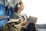 Young woman travelling by train with tablet and headphones