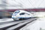 Train rides at high speed in winter around the snowy city industrial landscape