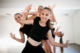 Group of fit happy children exercising dancing and ballet in studio together