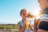 Children drinking orange juice outdoor