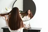 Beautiful young woman with healthy long hair looking in mirror at home
