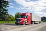 Czerwony duży rig popularnej maski półciężarówki przewożącej ładunek handlowy w suchej furgonetce naczepy poruszającej się po prostej szerokiej autostradzie
